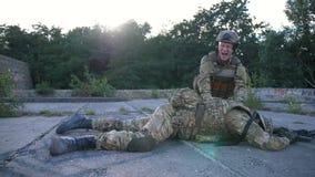 Den ilskna soldaten sörjer för den borttappade kamraten i armar arkivfilmer