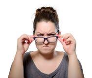 Den ilskna strikta kvinnan bär exponeringsglas, grimasstående royaltyfria bilder