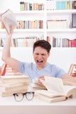 Den ilskna studenten som omges av böcker, kastar en bok Arkivbilder