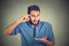 Den ilskna tokiga mannen som gör en gest med hans finger mot templet som frågar, är dig som är galen? arkivfoto