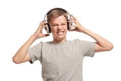 Den ilskna tonårs- pojken tar av hörlurar royaltyfria bilder
