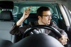 Den ilskna unga chauffören grälar med andra chaufförer Hans vänstra hand är på styrhjulet royaltyfri fotografi