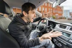 Den ilskna unga chauffören kör en bil och ropa royaltyfri bild