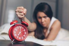 Den ilskna unga kvinnan dödar av ringklockan vid näven på sängen i morgonen royaltyfri fotografi