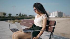 Den ilskna unga kvinnan med bärbara datorn fås en dåliga nyheter och att reagera till problemet arkivfilmer