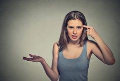 Den ilskna unga kvinnan som gör en gest att fråga, är dig som är galen? royaltyfria foton
