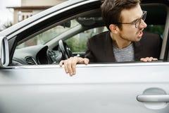Den ilskna unga mannen kikar från fönstret Han ser något bak hans bil arkivfoton
