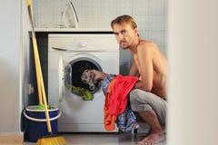 Den ilskna unga mannen laddar tvätterit in i tvättmaskinen Manligt hemmafru- eller ungkarlbegrepp arkivfoton