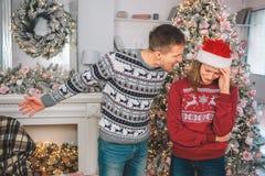 Den ilskna unga mannen står nästan kvinnan och skrin på henne Han punkter lämnade Modellen är uppriven Hon gråter De bär jul arkivbilder