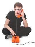 Den ilskna ungen skriker in i telefonen Royaltyfria Bilder