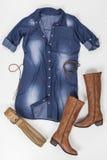 Den indigoblå tygklänningen med knappar, bältet och brunt startar på vit bakgrund arkivbild