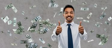 Den indiska affärsmanvisningen tummar upp över pengar arkivfoto