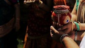 Den indiska bruden och hon föräldrar rymmer den röda bunken med juvlar i deras händer arkivfilmer