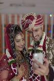 Den indiska hinduiska bruden & ansar en lycklig le parskyttesjälv med mobilen. royaltyfri fotografi