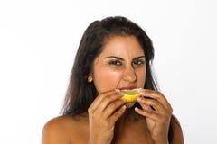 Den indiska kvinnan äter citronen arkivfoton