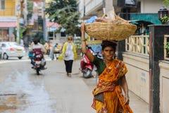 Den indiska kvinnan bär korgen på hans huvud på stadsgatan 11 februari 2018 Puttaparthi, Indien Royaltyfria Bilder