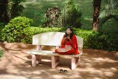 Den indiska kvinnan i sari sitter, i utomhus- och att skratta, medan talar mobiltelefonen 8 februari 2018 Sai Baba Ashram Puttapa Royaltyfria Bilder