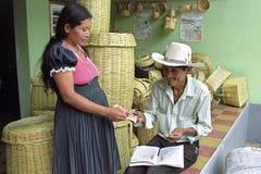 Den indiska kvinnan säljer vide- korgar till butiksinnehavaren royaltyfria bilder