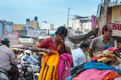 Den indiska kvinnan väljer kläder på den Russell marknaden i Bangalore Arkivbild