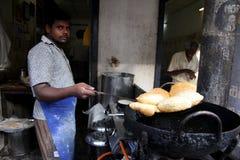 Den indiska mannen är den stående stekte purien, som är indisk mat Med en stor svart panna Men använd den olje- van vid småfisken Royaltyfri Bild