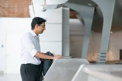 Den indiska mannen på flygplatsen kontrollerar in räknaren Arkivbild