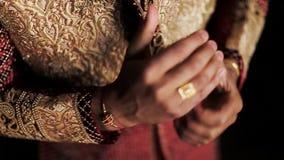 Den indiska mannen rymmer hans händer som står tillsammans i bröllopdräkt stock video
