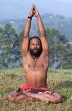 Den indiska mannen som mediterar i lotusblommayoga, poserar på grönt gräs i Keral Arkivfoto