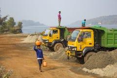 Den indiska unga mannen bär en trumma av vatten på hans huvud mot bakgrunden av gula lastbilar royaltyfri bild