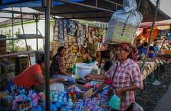 Den indonesiska kvinnan med en påse på hennes huvud köper grönsaker på den lokala gatamarknaden royaltyfria bilder