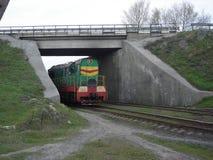 Den industriella lokomotivet passerar under en bro Arkivfoto
