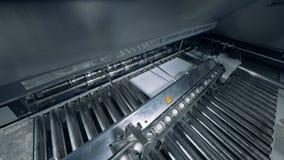 Den industriella maskinen släpper papper på den rörande transportören lager videofilmer