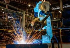Den industriella roboten svetsar den automatiska delen för enheten i bilfabrik Fotografering för Bildbyråer