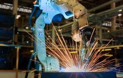 Den industriella roboten svetsar den automatiska delen för enheten i bilfabrik Royaltyfri Bild