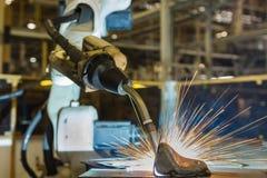 Den industriella roboten svetsar den automatiska delen för enheten i fabrik Royaltyfri Foto