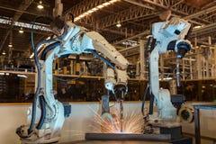 Den industriella roboten svetsar den automatiska delen för enheten i fabrik Fotografering för Bildbyråer