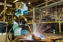 Den industriella roboten svetsar den automatiska delen i fabrik Royaltyfri Fotografi