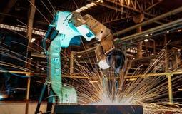 Den industriella roboten svetsar i automatisk delfabrik Royaltyfri Bild