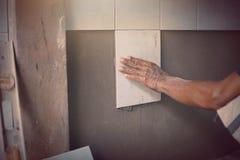 Den industriella tilerbyggmästarearbetaren renoverar väggen Arkivbild