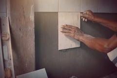 Den industriella tilerbyggmästarearbetaren renoverar väggen Arkivfoton