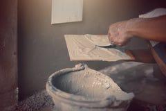 Den industriella tilerbyggmästarearbetaren renoverar väggen Arkivfoto