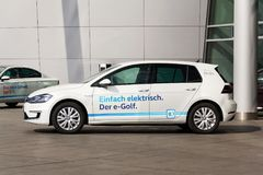 Den inkopplingshybrid- Volkswagen e-golf elbilen står vid uppladdningsstationen framme av Glasernen Manufaktur - genomskinlig fab Royaltyfria Bilder