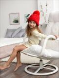 Den inomhus vinterståenden av flickan i en varm slags tvåsittssoffa beklär lite: den röda stack vinterhatten och vit kintted klän royaltyfri fotografi