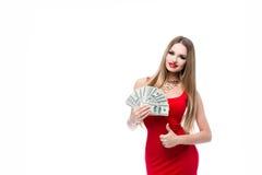 Den Insanely härliga unga kvinnan i den röda klänningen som rymmer många 100 dollarräkningar och visar, tummar upp alla bra Royaltyfri Bild