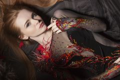 Den intressanta ståenden av en ljust rödbrun flicka i en klänning med mousserar a Royaltyfri Fotografi