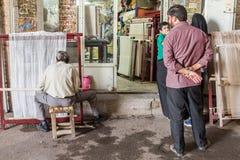 Den iranska familjen som ser en arbetare som producerar en filt på en weawing vävstol i hans, shoppar Mattor är en av huvudsaklig royaltyfri bild