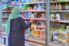 Den iranska kvinnan väljer mat på hylla i minimarket, Shiraz, Iran arkivfoton
