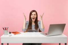 Den irriterade ilskna kvinnan i tillfällig kläder som skriker den fördelande handen, sitter arbete på det vita skrivbordet med de arkivbilder