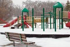 Den iskalla lekplatsen och parkerar bänken Arkivbild