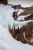 Den iskalla vattenfallet på vaggar klippan i vintertid Arkivbilder