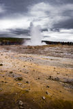 Den isländska geyseren, Strokkur som får utbrott in i ett dramatiskt molnigt Royaltyfri Foto